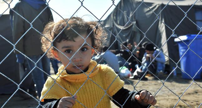 A girl holds on to a fence at a transit camp housing migrants and refugees in Slavonski Brod on November 4, 2015. (AFP Photo)