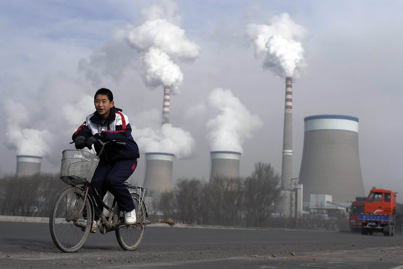 A Chinese boy cycles past cooling towers of a coal-fired power plant in Dadong, Shanxi province, China.