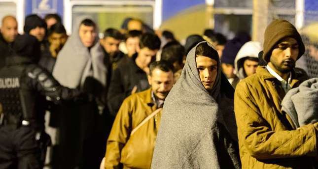 Migrants keep warm using blankets as they walk toward a refugee center in Sentilj, after arriving by train.