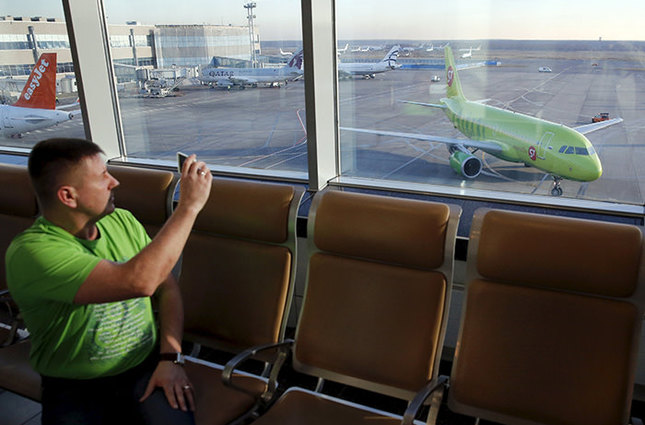 A man takes pictures, with a plane (R) of S7 airlines seen in the background, at Domodedovo airport outside Moscow, Russia, November 6, 2015 (Reuters Photo)