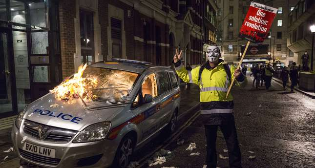 An anti-capitalist protester wearing a Guy Fawkes mask holds a placard as he stands alongside a burning police car during the Million Masks March, organised by the group Anonymous, in London on November 5, 2015. (AFP Photo)