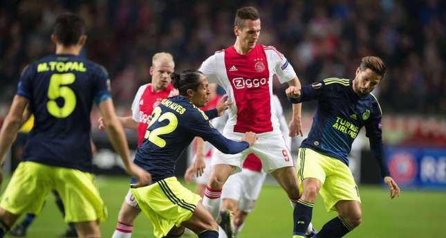 Ajax' Polish striker Arek Milik (2nd R) vies with Fenerbahçe's Brazilian midfielder Diego (C) and Portuguese defender Bruno Alves (R) during the UEFA Europa League football match in Amsterdam.
