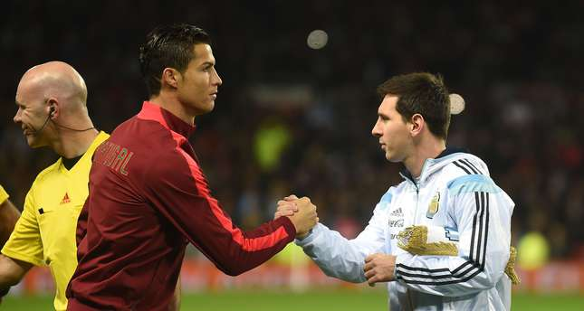Argentina striker Lionel Messi (R) shakes hands with Portugal's striker Cristiano Ronaldo (L) ahead of kick off of the international friendly football match between the Argentina and Portugal in Manchester on November 18, 2014. (AFP Photo)