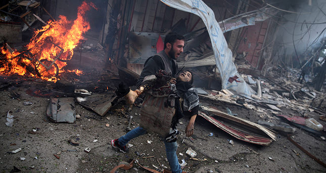 A Syrian man carries the body of a child killed in a reported air strike by government forces in the rebel-held area of Douma, east of the capital Damascus, on November 7 (AFP Photo)