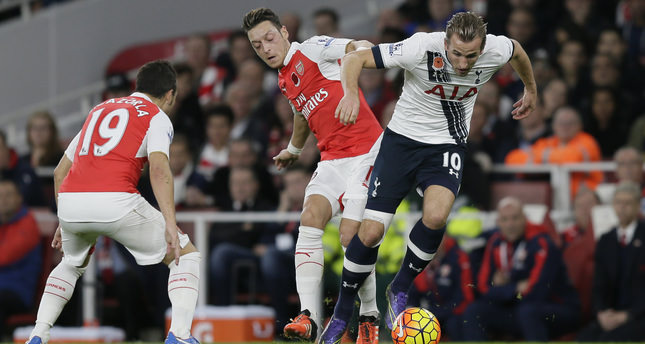 Arsenal's Mesut Ozil, centre, competes for the ball with Tottenham's Harry Kane during the English Premier League soccer match between Arsenal and Tottenham Hotspur at the Emirates Stadium in London, Sunday Nov. 8, 2015. (AP Photo)