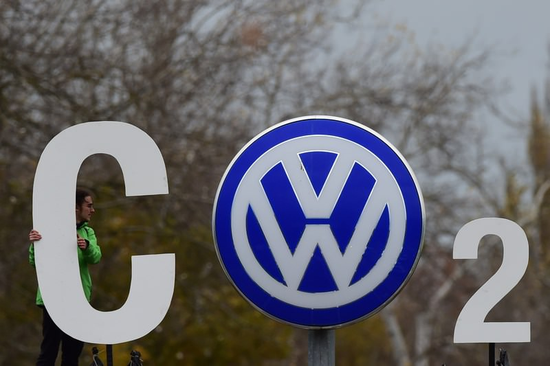 An activist of Greenpeace holds a giant letter to display ,CO2, around the logo of German car maker  VW  on November 9, 2015. (AFP Photo)