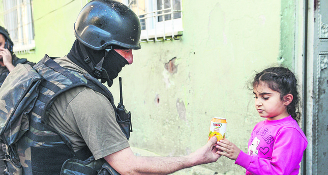Law enforcement agents are in the process of dismantling the PKK's urban wing while locals are largely supportive of the efforts. A police handing fruit juice to a local girl.