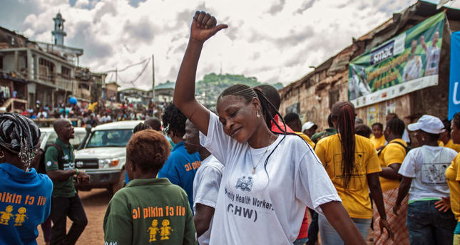 A woman celebrates with others as the country is declared Ebola free in the city of Freetown.