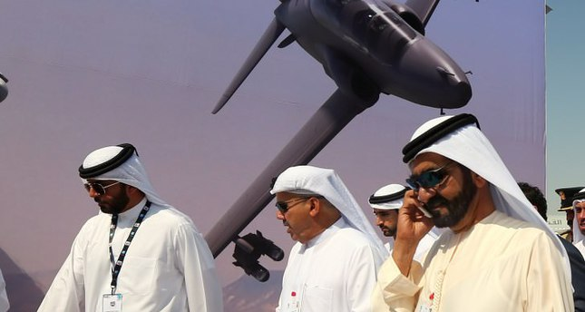 Sheikh Mohammad bin Rashed al-Maktoum (R), Prime Minister of the UAE and ruler of Dubai, talks on the phone while walking past a poster of a U.S. jetfighter during the Dubai Airshow.