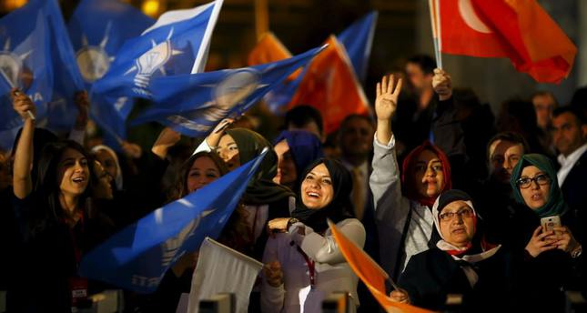 Women wave flags outside AK Party headquarters in Ankara, the day after the party swept back to a parliamentary majority.