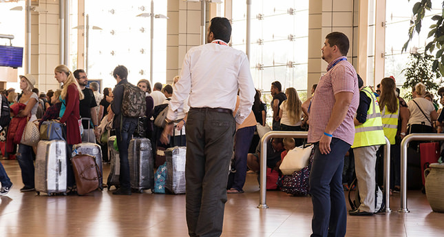 Travel company agents look at the line of tourists at the airport of Sharm el Sheikh, Egypt, on Saturday, Nov. 7, 2015. (AP Photo)
