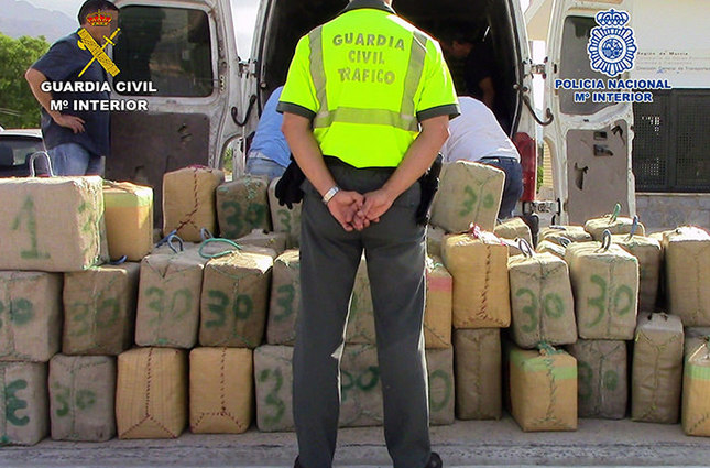 Spanish Home Ministry on 07 October 2015 shows a Spanish Civil Guard standing in front of packages containing hash in Murcia, southeastern Spain (EPA Photo)