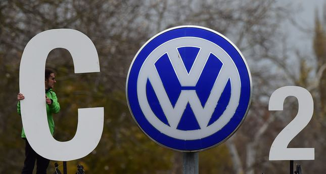 An activist of Greenpeace holds a giant letter to display CO2 around the logo of German car maker  VW  on November 9, 2015. (AFP Photo)