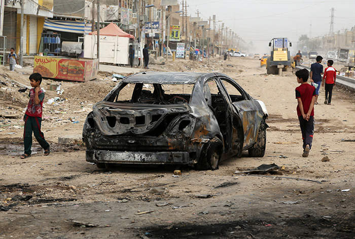 Civilians inspect the aftermath of a car bomb explosion in Husseiniya, about 13 miles (20 kilometers) northeast of Baghdad, Iraq (AP Photo)