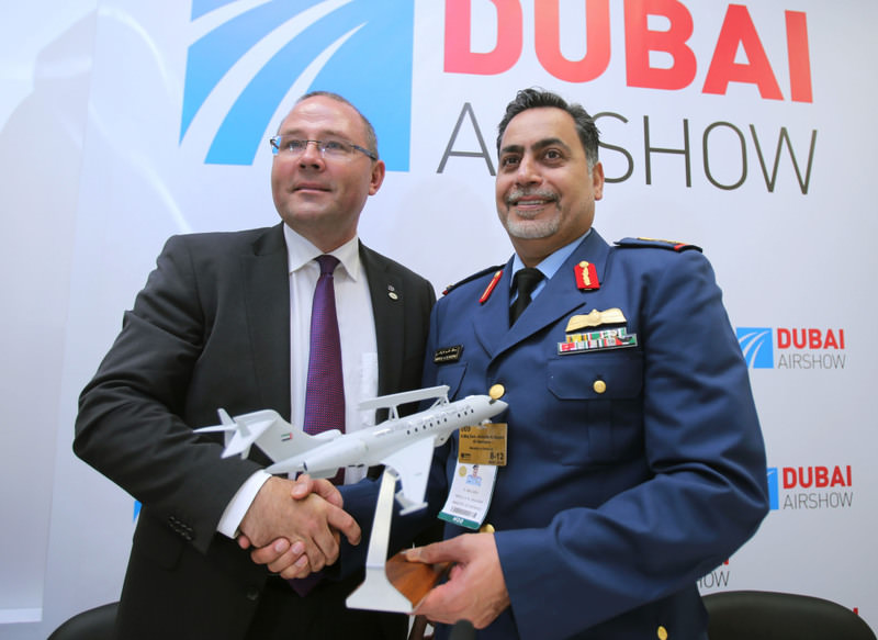 Saab President and CEO Hakan Buskhe (L), and UAE Major General Abdullah al-Hashimi shake hands as they hold a model of the Bombardier Global 6000 aircraft at the DubaiAirshow.