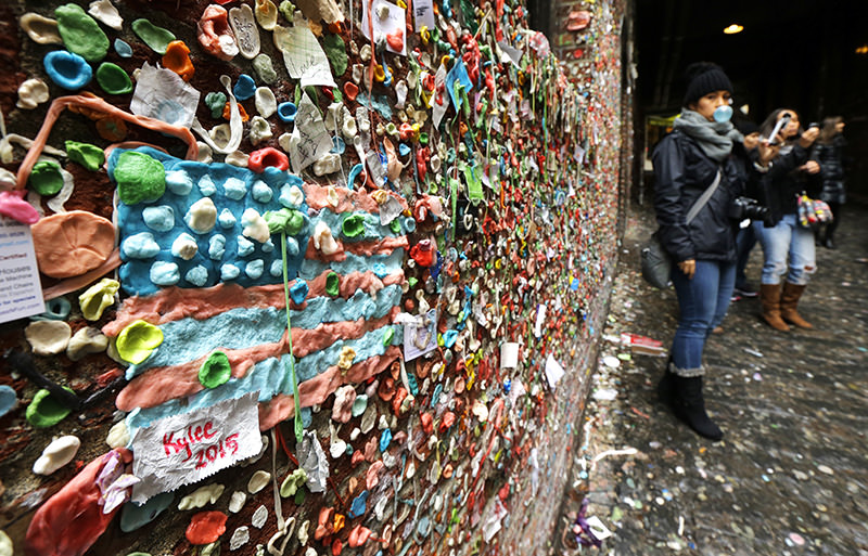 The likeness of an American flag made from pieces of gum sticks to a wall at Seattle's ,gum wall, at Pike Place Market, Monday, Nov. 9, 2015 (AP Photo)