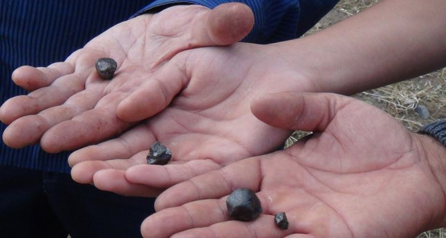 Villagers show pieces of meteorite they found. They say they are paid as much as $60 per piece.