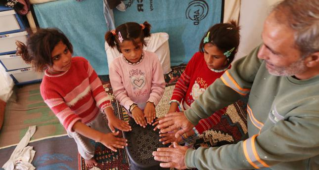 A family of Syrian refugees tries to warm up around a heater in a tent in Suruç.