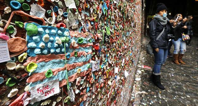 The likeness of an American flag made from pieces of gum sticks to a wall at Seattle's gum wall at Pike Place Market, Monday, Nov. 9, 2015 (AP Photo)