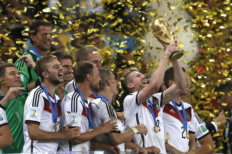 Germany's forward Andre Schuerrle (C) holds the World Cup as he celebrates with teammates after his team's victory in the final between Germany and Argentina.