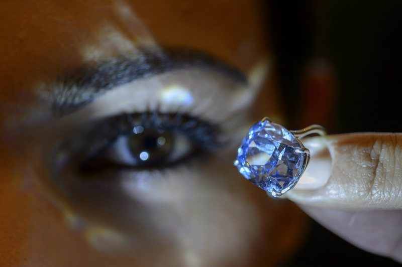 Sotheby's employee displays the rare Blue Moon Diamond during a preview at Sotheby's, in Geneva, Switzerland, Wednesday, Nov. 4, 2015. (AP Photo)