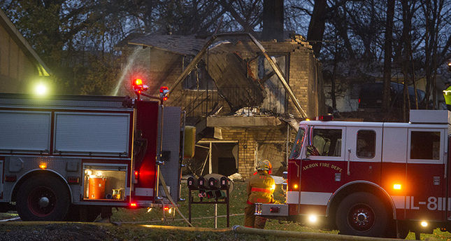 Firefighters work at the scene where authorities say a small business jet crashed into an apartment building in Akron, Ohio, Tuesday, Nov. 10, 2015 (AP Photo)