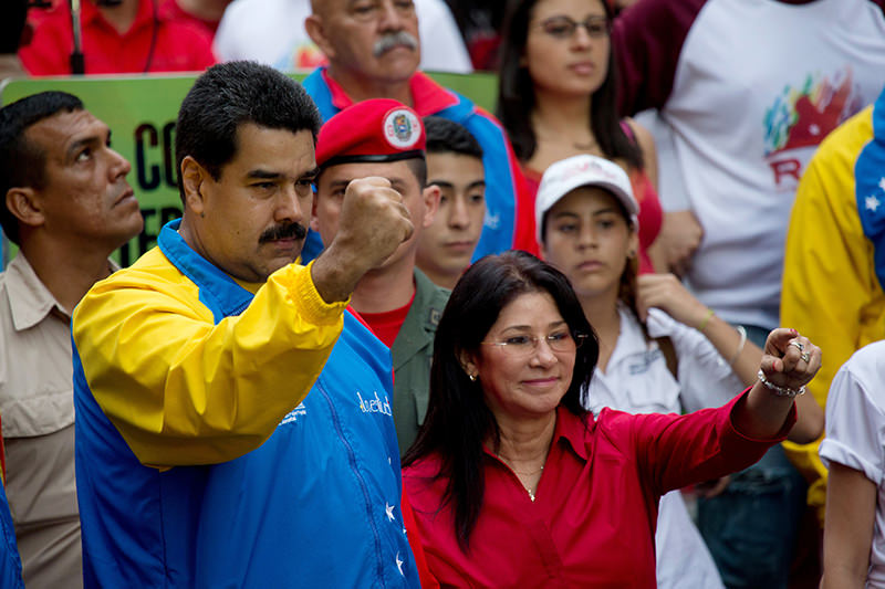 In this Oct. 18, 2014 file photo, Venezuela's President Nicolas Maduro and first lady Cilia Flores, greet supporters as they arrive for a march for peace in Caracas, Venezuela. (AP Photo)