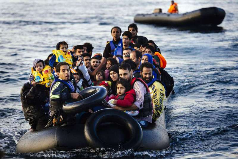 Refugees arrive on a raft to the Greek island of Lesbos on Oct. 14.