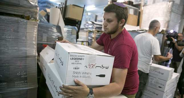 A worker carries boxes containing wine bottles and will have to label them as produced in occupied territories to export the EU countries.
