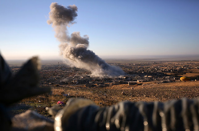 Smoke believed to be from an airstrike billows over the northern Iraqi town of Sinjar on Thursday, Nov. 12, 2015.