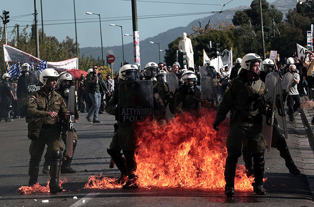 Greek police stand guard amid molotov cocktails thrown by protesters during a massive demonstration as part of a 24-hour general strike in Athens on November 12, 2015 AFP Photo
