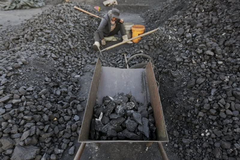 A villager selects coal at a coal depot in China's Heilongjiang province. China is the biggest investor in fossil fuel production according to a report, spending $77 billion annually through state-owned enterprises.
