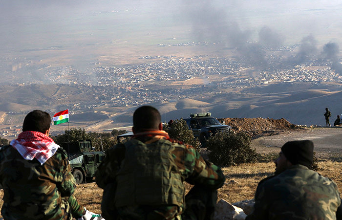 Iraqi Peshmerga fighters look on as smoke billows during an operation in the northern Iraqi town of Sinjar on November 12, 2015 (AFP Photo)