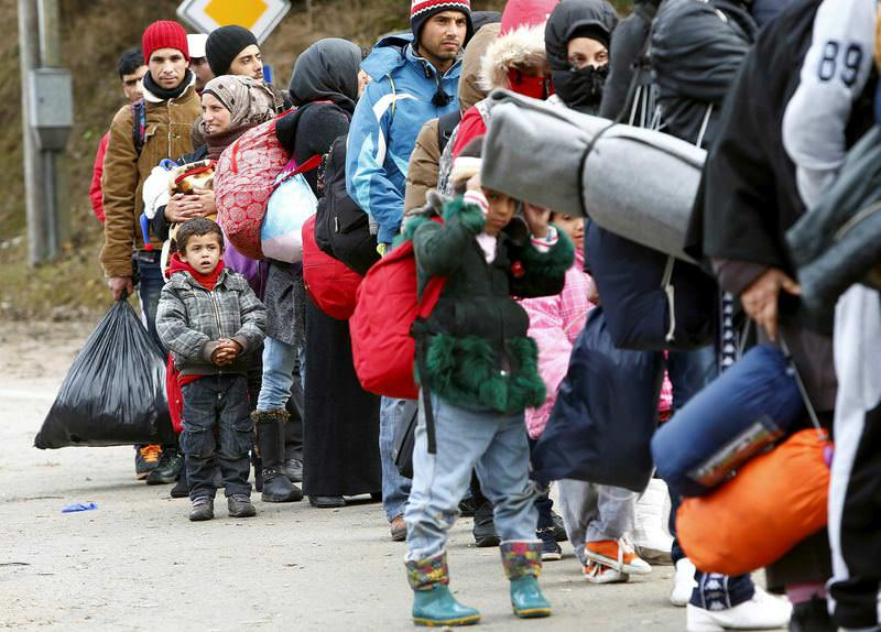 Migrants stand in a queue before passing through the Austrian-German border from Austria.