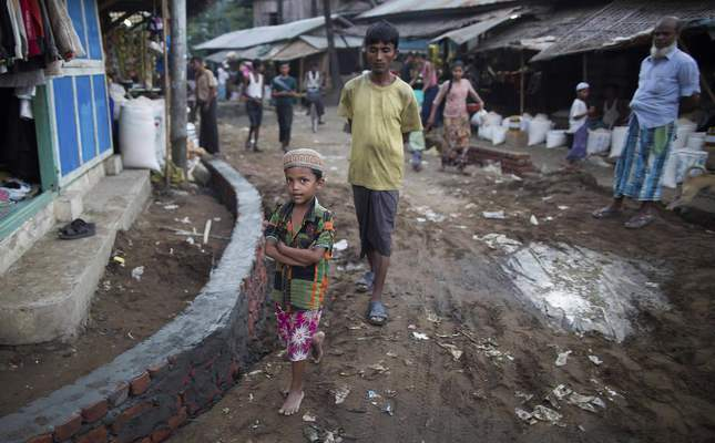 A Rohingya boy and elders walk at a market near Thel-Chaung displacement camp in Sittwe located in Rakhine State. (AFP Photo)
