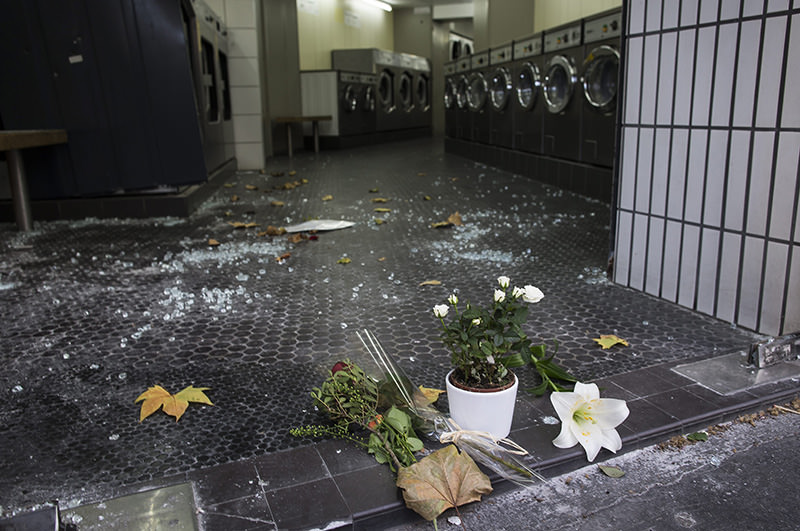 People lay flowers and candles in front of a laundromat near the Casa Nostra restaurant in Paris, France, 15 November 2015 (EPA photo)