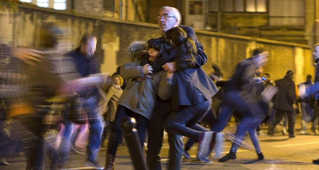 A man carries two children after panic broke out among mourners who payed their respect at the attack sites at restaurant Le Petit Cambodge and the Carillon Hotel in Paris, Sunday, Nov. 15, 2015. (AP Photo)