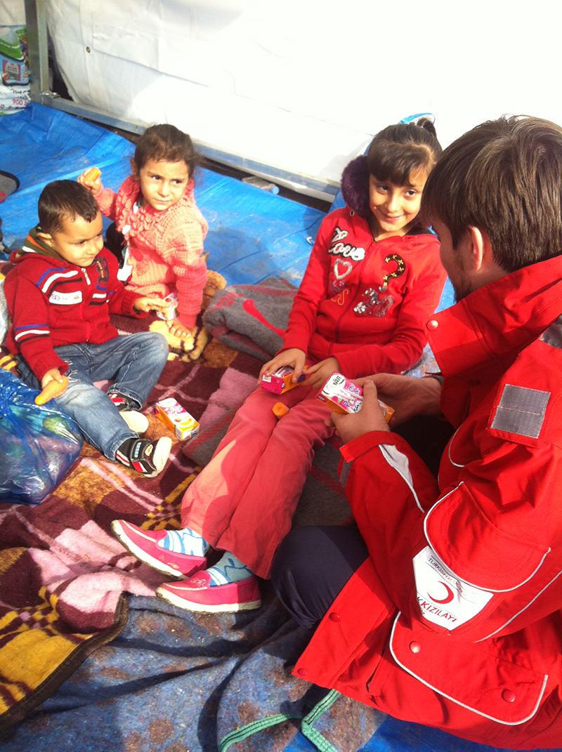 Güllüoğlu speaking with children in refugee camps.