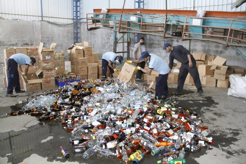 Workers demolishing bottles of bootleg alcohol, which has claimed 34 lives since last month in Istanbul.