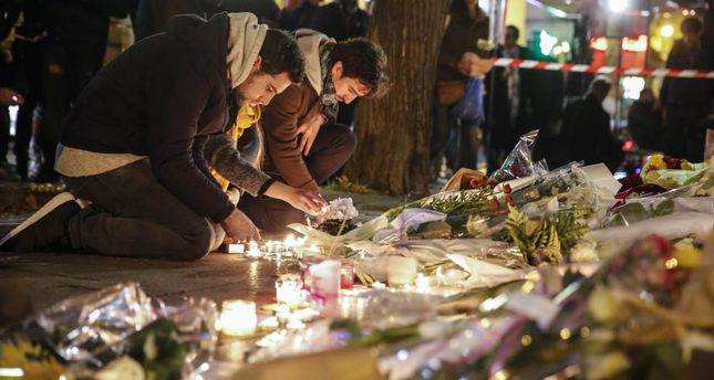 People place flowers and light candles in tribute to the victims of the Friday's attacks in Paris.
