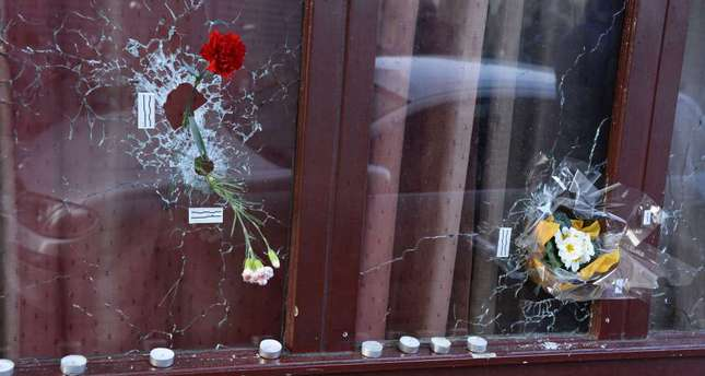 Flowers placed in bullet holes at a memorial site outside of Carillon Bar, for victims of the Nov. 13 terrorist attacks in Paris.