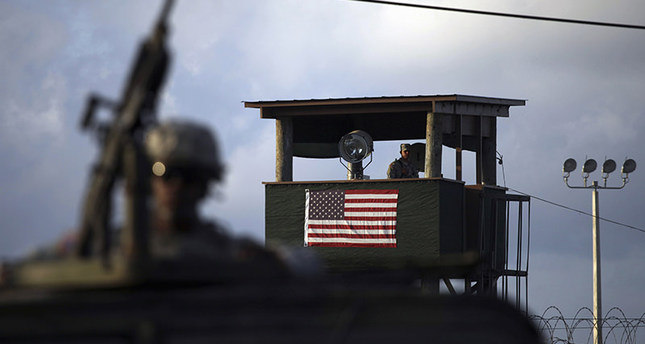 In this March 30, 2010 file photo, reviewed by the U.S. military, a U.S. trooper mans a machine gun in the turret on a vehicle as a guard looks out from a tower in front of the detention facility at Guantanamo Bay U.S. Naval Base, Cuba (AP Photo)