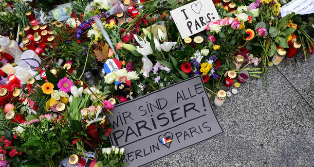 A message reads  We are all Parisians - Berlin loves Paris  amount flowers and candles on the ground outside the French embassy in Berlin, on November 16, 2015. (AFP Photo)