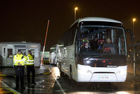 Syrian refugees are driven away in a convoy of buses after landing at Glasgow airport, Scotland on November 17, 2015 (AFP Photo)
