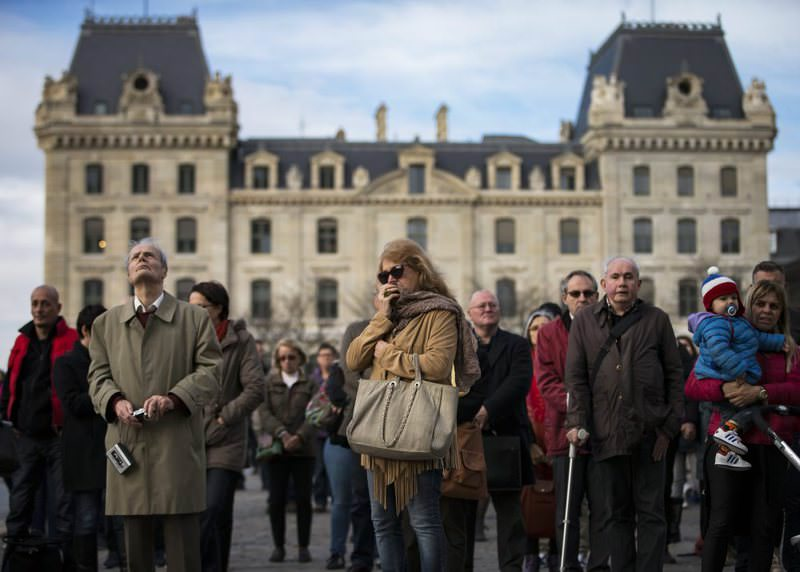 People gather to hold a minute of silence in front of the Notre-Dame Cathedral in Paris.