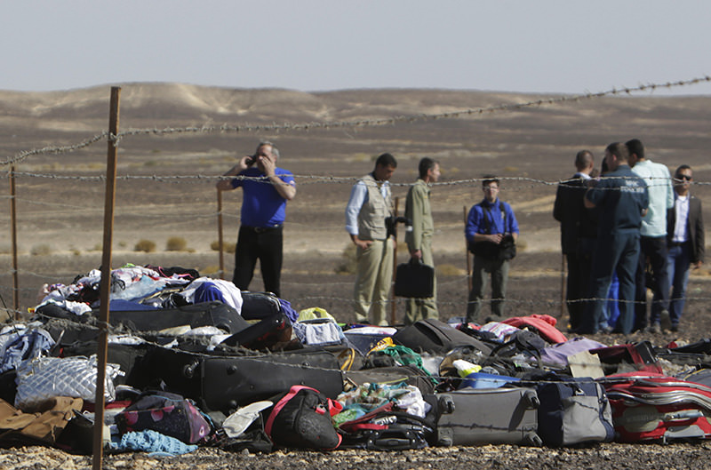Russian investigators stand near debris, luggage and personal effects of passengers (AP photo)