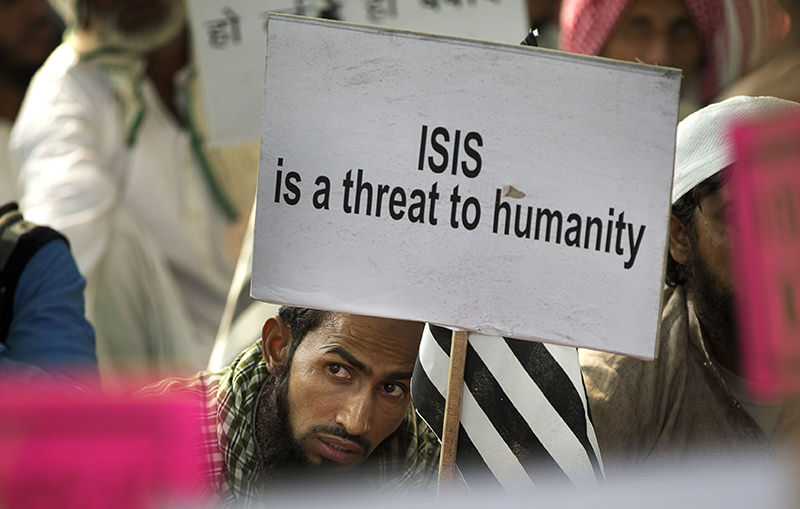 An Indian Muslim man holds a banner during a protest against ISIS (aka Daesh), and Friday's Paris attacks, in New Delhi, India, Wednesday, Nov. 18, 2015 (AP Photo)