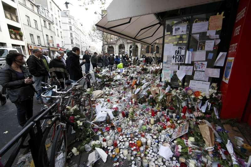 People looking at the flowers, candles and messages left in tribute to victims in front of La Belle Equipe cafe, one of the scenes of the deadly attacks in Paris.