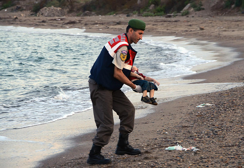 The image Blasio shows durnig his speech: A Turkish gendarmerie officer carries three-year-old Aylan Kurdi's body (DHA Photo)