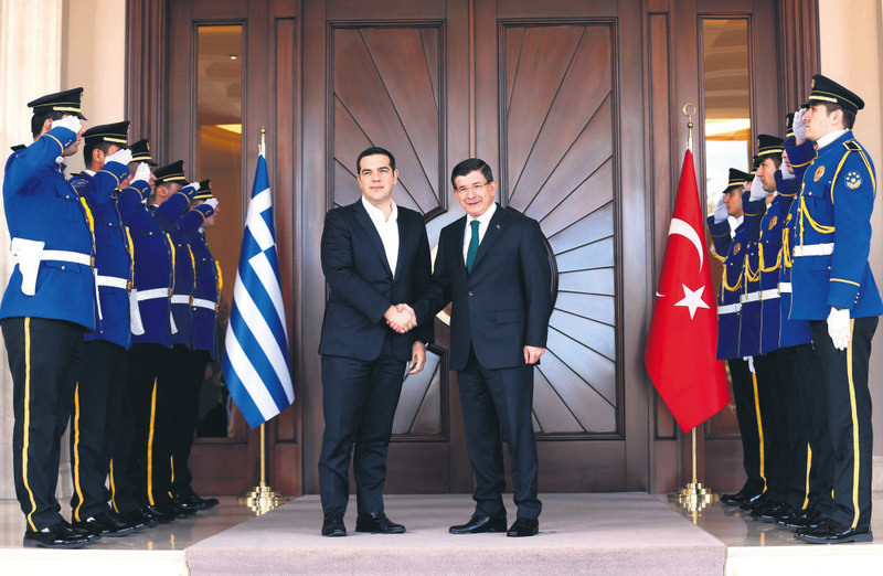 PM Ahmet Davutou011flu (R) shakes hands with his Greek counterpart Alexis Tsipras upon his arrival for a meeting in Ankara.